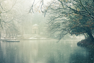 Little temple in a pond of the Park of Monza surrounded by winter snow covered trees, Italy