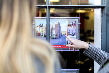 Couple looking at a property advert in the window of an estate agents or real estate shop window in England in the United Kingdom
