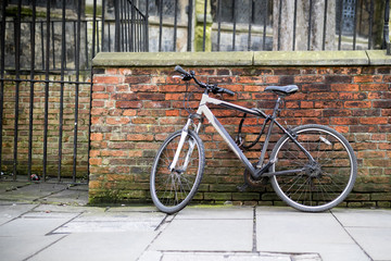 Mountain bikes padlocked against a brick wall as part of the cycle to work scheme or the Transport for London bicycle scheme in the UK