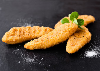 Fried chicken dippers on stone board with salt