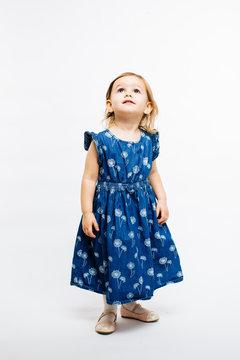 Full body portrait of a cute little preschool girl looking up on white background