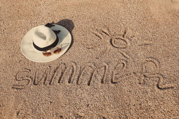 A hat and sunglasses lie on the sand. Beach vacation.