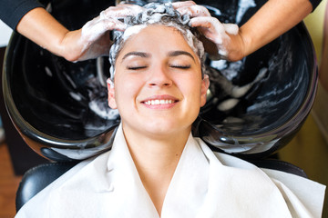 Beautiful young girl enjoying hair washing in hairdressing salon.