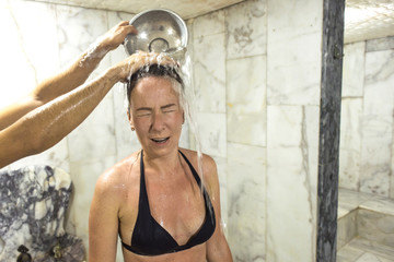 the girl is poured water in the Turkish hammam