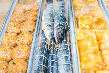 Closeup of many herring fish whole eyes plastic wrapped, cakes burgers in seafood market display