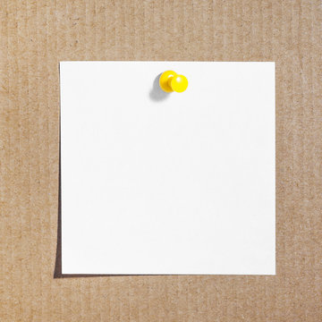 White memo card attached with yellow pin to brown cardboard.