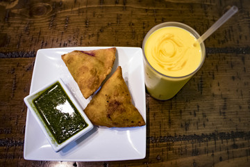 Two Samosas on a White Rectangle Plate with Mint Chutney with a Glass of Mango Lassi on the Right