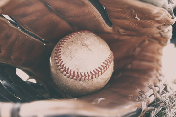 Athletic American sport shown with dirty ball in leather baseball glove.