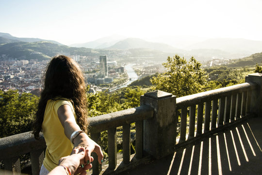 girl hand holding looking an over view of bilbao, in  artxanda a mountain near the city, fly view of bilbao, guggenheim and iberdrola tower  Bilbao, Spain august, 2017
