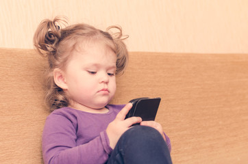 Little girl playing smartphone sitting on sofa