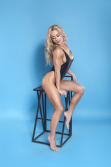 Sexy caucasian bodybuilder woman posing on a neutral blue background, showing her perfect body. She wearing black swimsuit