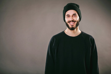 Smiling bearded brutal  stylish hipster wearing a blank black longsleeve shirt, black hat and black jeans against grey wall background looks at the camera