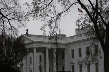 A U.S. Secret Service Agent keeps watch atop the White House in Washington