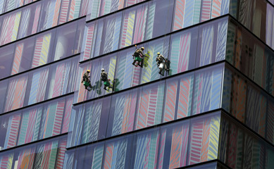 Workers clean the windows of a building in the San Isidro financial district in Lima