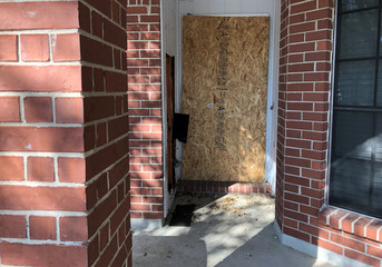 The doorway of a home that was hit with a fatal parcel bomb on March 2, 2018 is seen boarded-up in Austin