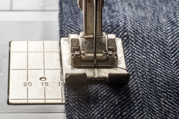 sewing machine sews denim fabric