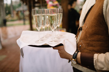 waiter brings glasses of champagne on a tray
