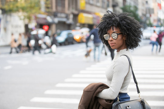 African American Woman in city scene wearing mirrored sunglasses