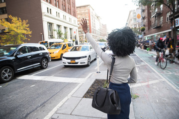 Woman hailing a taxi cab on a busy city street