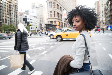 Beautiful African American Woman with black curly hair looking back in New York City