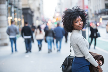 Woman with black, curly hair looking back and smiling