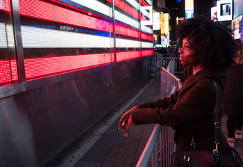 African American Woman looking at bright sign