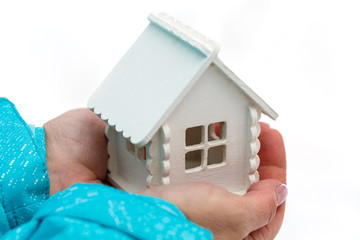 Small toy house lies in the women's hands on the white background