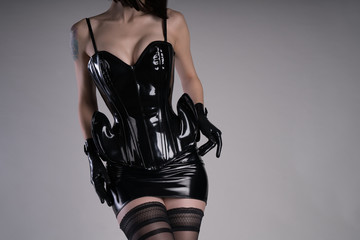 Sensual woman dressed in black latex corset and mini skirt