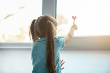 Little girl with red heart near window. Autism concept