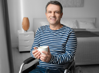 Mature man in wheelchair drinking coffee indoors