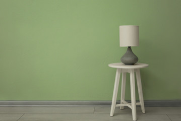 Elegant lamp on small table near color wall