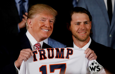 U.S. President Donald Trump poses for a portrait with Josh Reddick of the Houston Astros, and the rest of the 2017 World Series Champions after having been gifted a custom jersey in the East Room at the White House in Washington