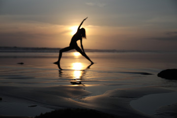 Silhouette of woman doing yoga on the beach at sunset