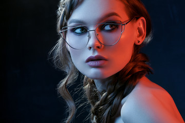 Close up studio portrait of beautiful woman with smoky eyes makeup wearing transparent glasses with metallic frame, posing in blue and red lights. Beauty, advertising concept. Copy, empty space