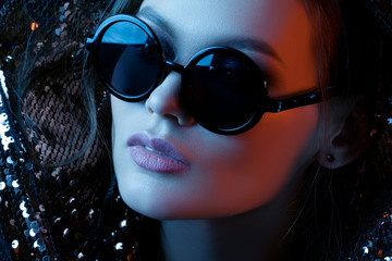 Close up studio portrait of young beautiful sexy woman wearing stylish black round sunglasses, posing in blue and red lights. Fashion, beauty, night party, advertising concept.