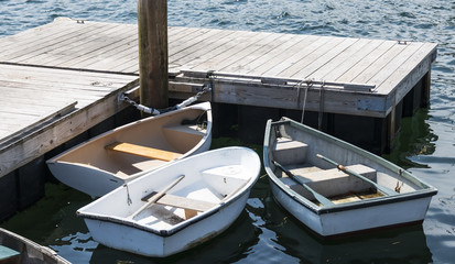 Three row boats with oars tied to a dock