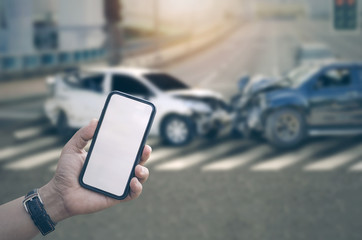 Man hand holding smartphone with blank screen and blur image of car crash accident background