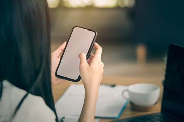 Cropped image of female hands holding smart phone with blank screen for online shopping over the desk