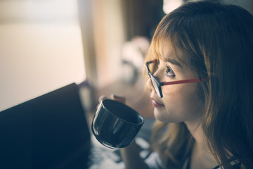 Close up image of young woman wearing glasses holding cup of coffee sitting in cafe,vintage style