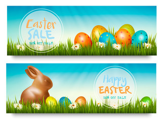 Two easter sale banners with colorful ggs in grass and a chocolate bunny. Vector.