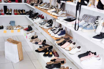 Shelves with sneakers in the shoes store