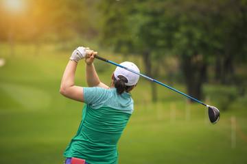 Deurstickers Golf golfer teeing golf ball to hole on golf course