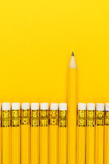 row of yellow pencils with erasers. leadership concept