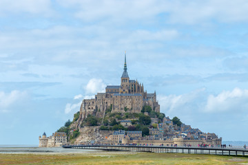 Panoramic view of famous Le Mont Saint-Michel tidal island in beautiful twilight during grey blue hour at dusk, Normandy, northern France
