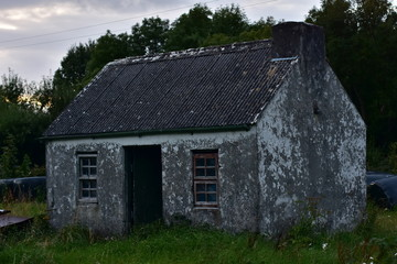 Weathered tiny country house on abandoned property in late evening light.