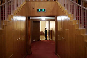 A member of the security personnel stands at his position before the fourth plenary session of the National People's Congress (NPC) at the Great Hall of the People in Beijing