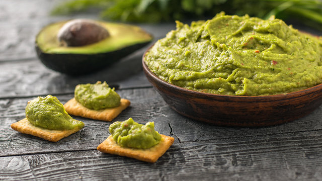 Half an avocado and a bowl of guacamole on rustic table. Diet vegetarian Mexican food avocado.