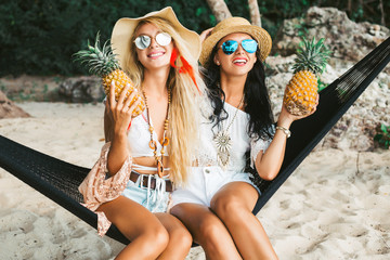 Two cute beautiful girls in boho style dressed shirts shorts light cape bracelets necklaces, in the hair decorative colored feathers, straw hats, with pineapple in their hands sit in a hammock