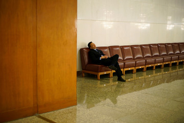 A man rests before the fourth plenary session of the National People's Congress (NPC) at the Great Hall of the People in Beijing