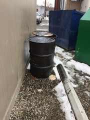 Closeup of two dirty greasy barrels outside building with garbage and recycling bin.